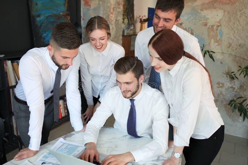 Start commercieel team op vergadering in modern helder bureaubinnenland en het werken aan laptop stock foto