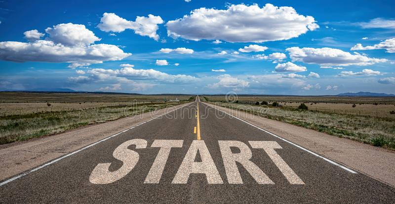 Start concept. Text sign on a long straight road, blue sky background stock photography