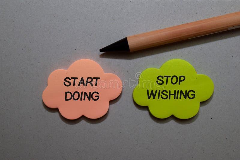 Start Doing of Stop met schrijven op kleverige notities die op Office Desk zijn geïsoleerd stock afbeelding