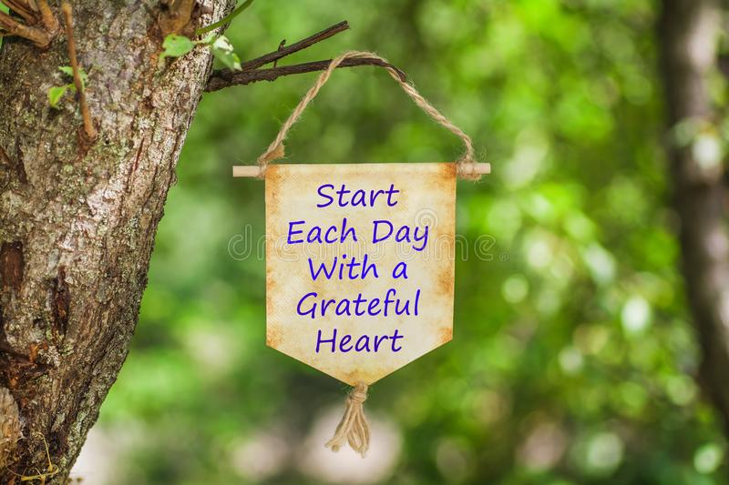 Start each day with a grateful heart on Paper Scroll. Hanging from the tree with nature green bokeh light background stock photo
