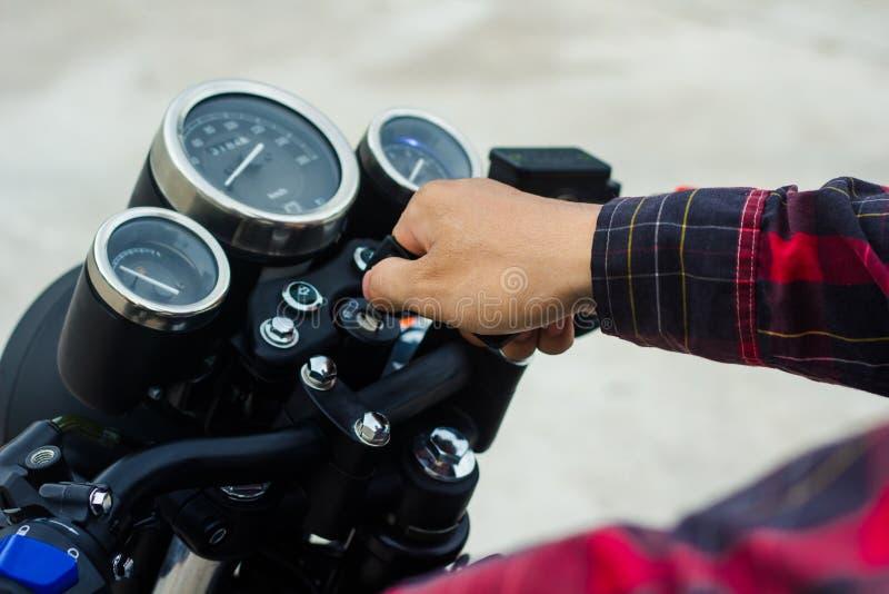 Start för hand för man` s som motorcykeln stämmer arkivfoto