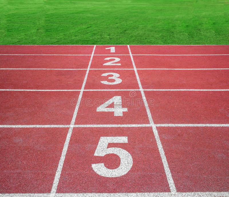 Start or finish position on running track with green field.  stock images