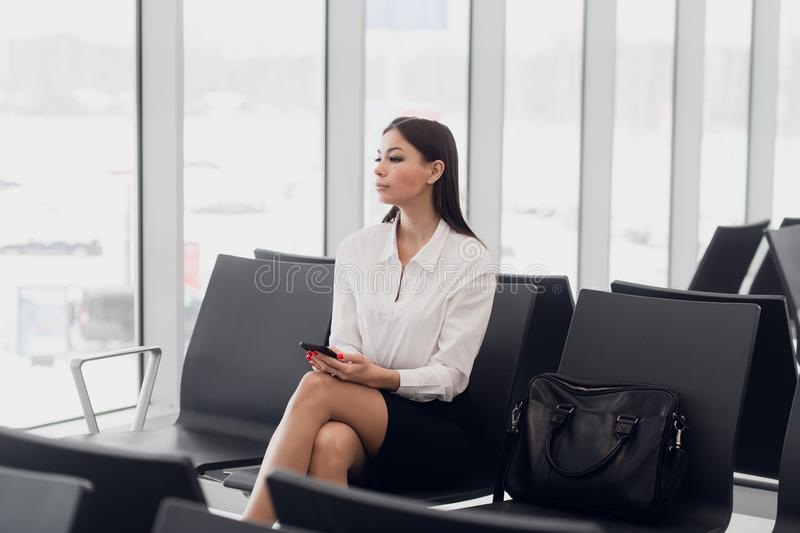 Start of her journey. Beautiful young woman looking out window at flying airplane while waiting boarding on aircraft in stock images