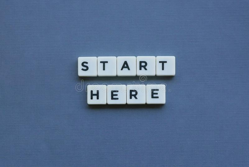 ' Start Here ' word made of square letter word on grey background. Journey, way, success, business, concept, forward, path, idea, go, direction royalty free stock photo