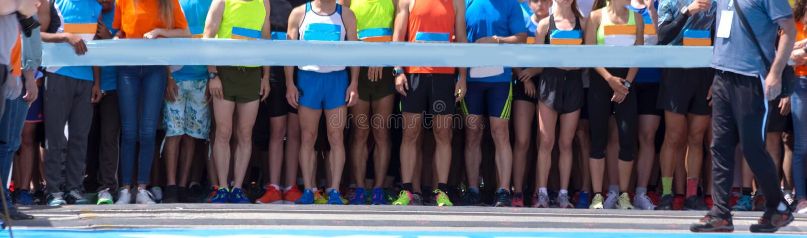Start lin in road marathon competition feet background. Athletes royalty free stock photography