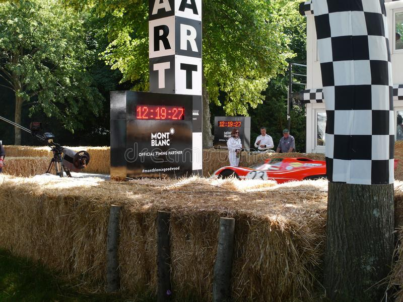 Start line at Goodwood Festival of Speed. UK. Start line at Goodwood Festival of Speed. Ferrari speeding back to start. Officials and straw bails in dappled tree royalty free stock photography