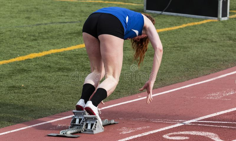 High school girl sprinter coming out of the blocks royalty free stock photo