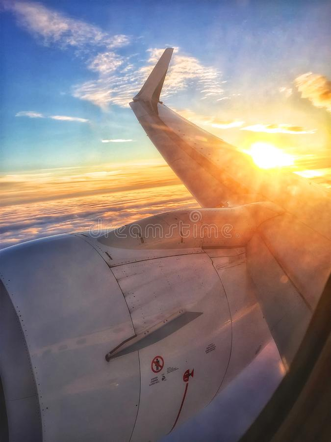 Sunset Over the Wing of a Plane. The Start of a New Adventure- The sun sets in the background as the plane turns towards the coming of the night. Morning will