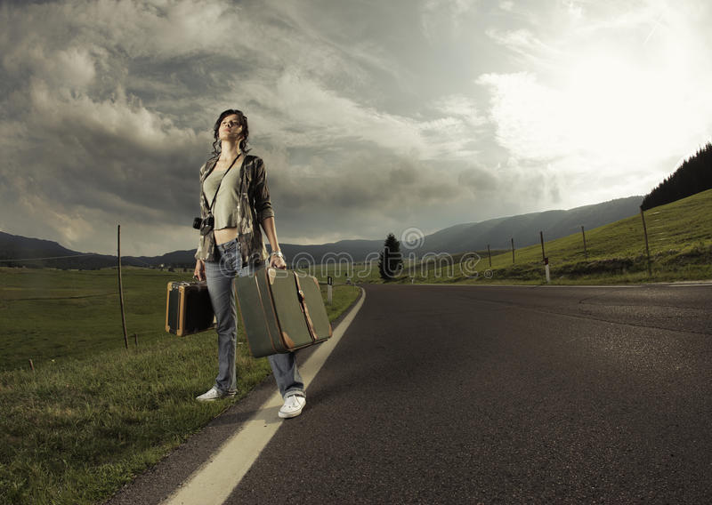 Start a new life. Young woman with old suitcase is ready to start. Copy space stock photo