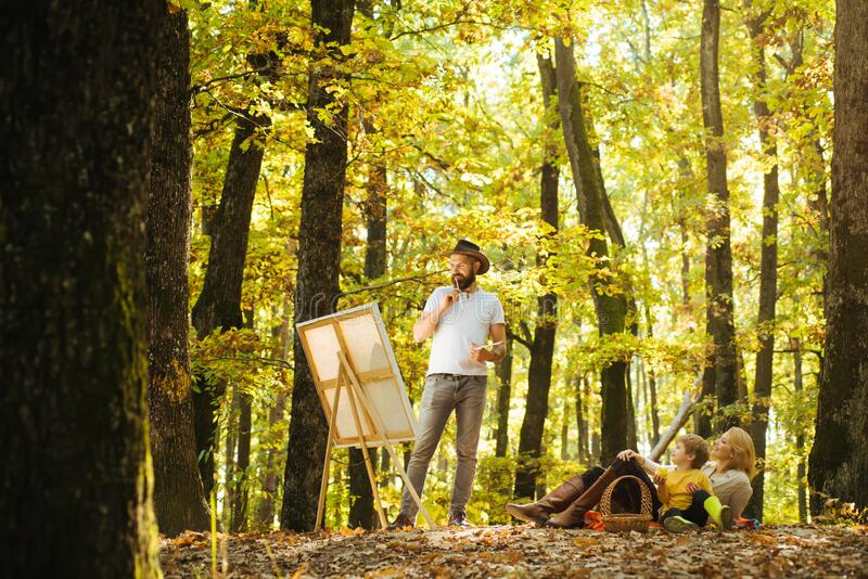 Start new picture. Portrait of young bearded smiling middle age white man artist drawing in open plein air outside with royalty free stock photos