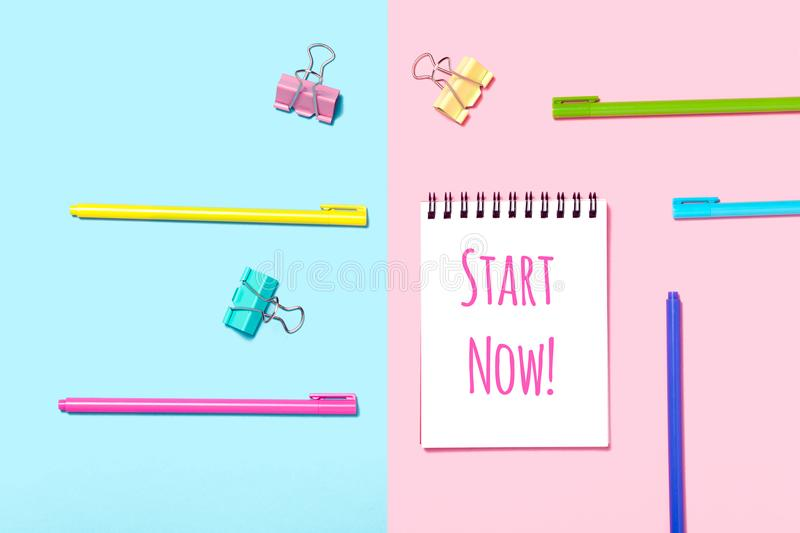 Start Now motivation in Notebook or notepad on blue and pink background. Creative minimalism chancery concept. Top view, flat lay stock image