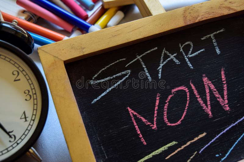 Start now phrase colorful handwritten on chalkboard, alarm clock with motivation and education concepts. royalty free stock image