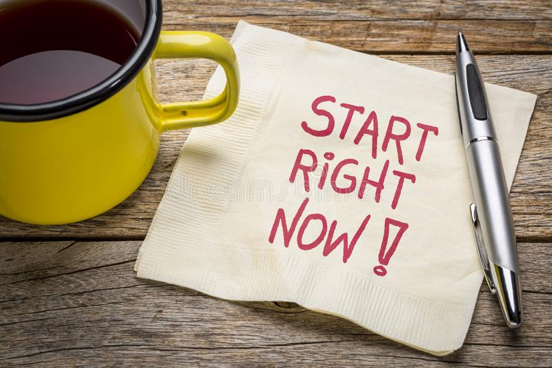 Start right now - motivational note on napkin. With a cup of tea royalty free stock photography