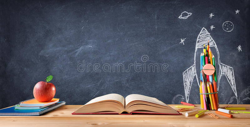 Start School Concept - Supplies On Desk And Rocket Drawn. On Blackboard stock images