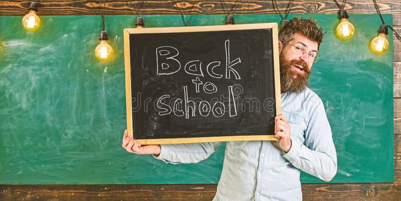 Start of school year concept. Teacher on cheerful face holds blackboard with title back to school. Man with beard. Welcomes students, chalkboard on background stock photo