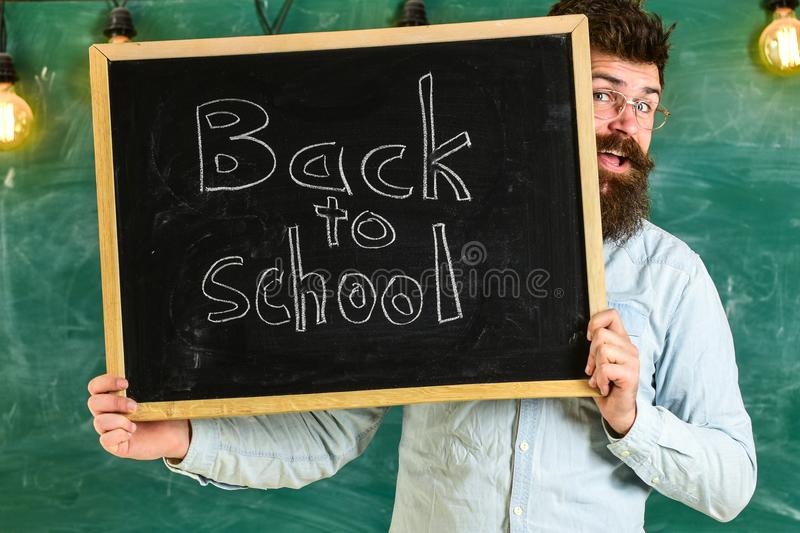 Start of school year concept. Teacher peeking out of chalkboard. Man with beard welcomes students, chalkboard on royalty free stock photos