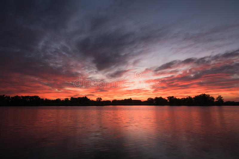 Start of Sunrise at the Fishing Pond. Purple and orange hues as sunrise begins over the local fishing pond royalty free stock photography