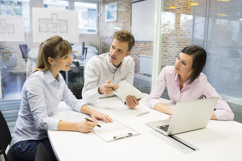 Start-up affärslag i mötet som arbetar på datoren arkivbild