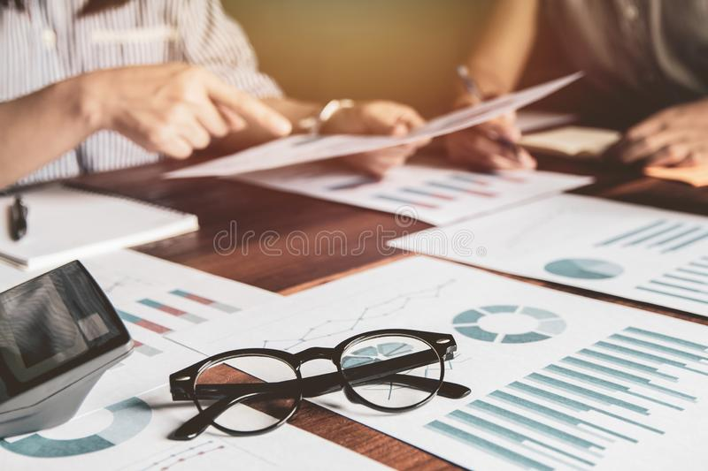 Start up business. Close-up glasses with people holding pen ,Team work meeting point to discuss the graph up and down of economy a royalty free stock photo