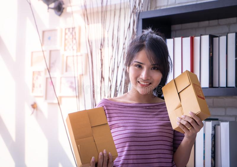 Start up business woman holding delivery boxes ready to send stock image