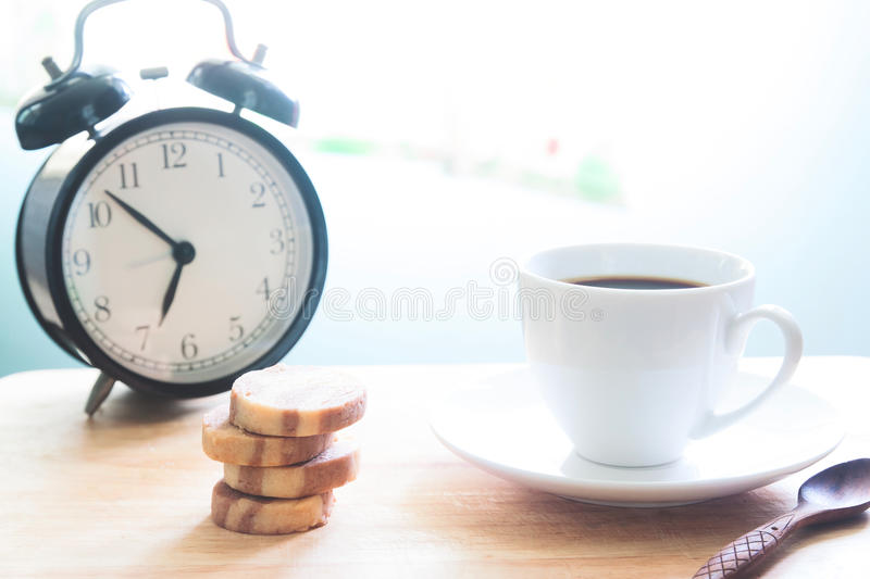 Start up concept with coffee cup, cookies and alarm clock royalty free stock photo