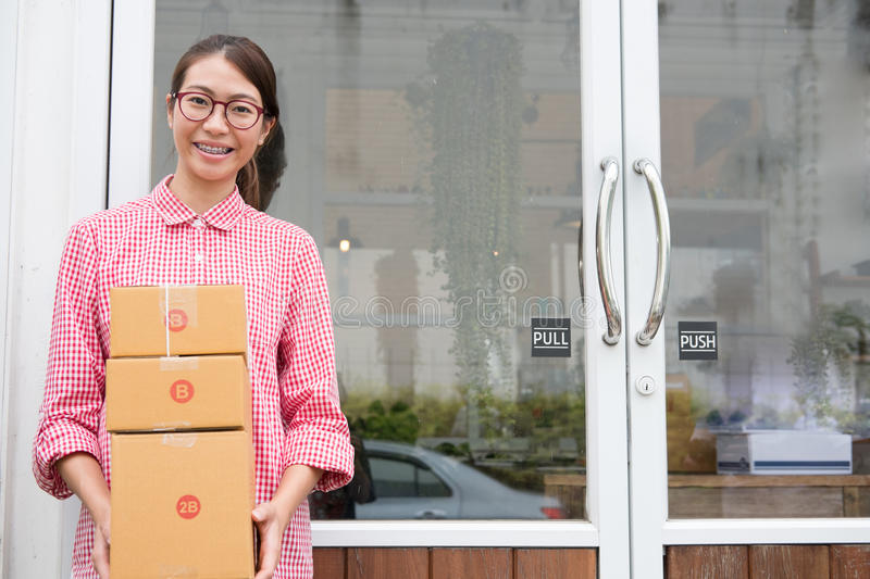 Start up small business owner holding parcel box at workplace. f. Young start up small business owner holding parcel box at workplace. freelance woman royalty free stock photos