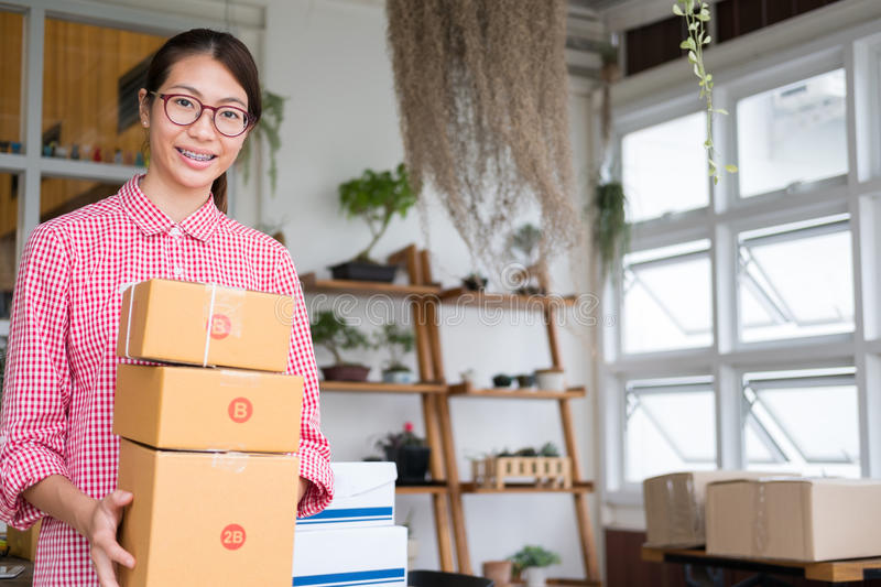 Start up small business owner holding parcel box at workplace. f stock photography