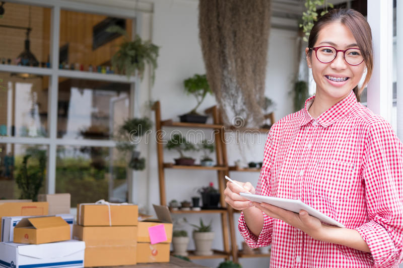 start up small business owner working with digital tablet at workplace. freelance woman entrepreneur SME seller check product royalty free stock photos