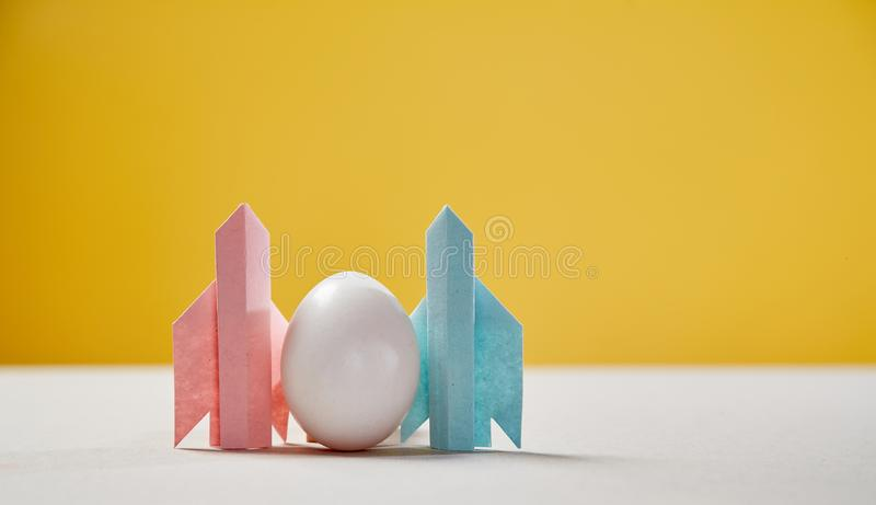 Start up and success. New business, aspirations, and investment concept. Egg soaring on the wings of rockets stock photos