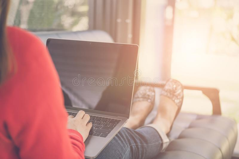 Start up woman typing on computer while sitting on sofa at home. Young start up woman typing on computer while sitting on sofa at home. freelance female adult royalty free stock images