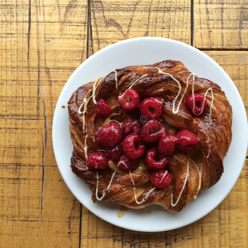 Start your day with homemade Gourmet danish pastry raspberry and icing on wood table royalty free stock photography