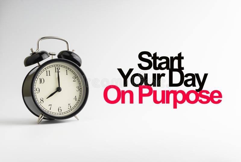 START YOUR DAY ON PURPOSE inscription written and alarm clock on white background royalty free stock images