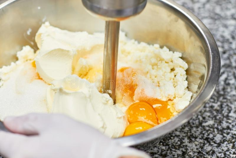Starta stirringkräm i bunke med den motoriska blandaren som bakar kakan royaltyfri foto