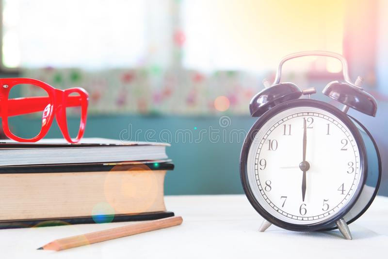 Starta upp begreppet, ringklockan, böcker och exponeringsglas i morgonen arkivbilder