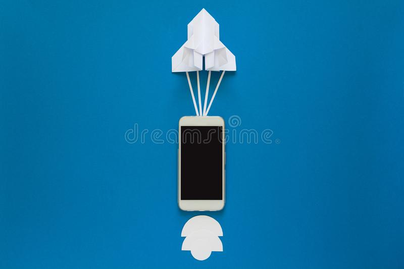 Starta upp eller fasta anslutningsbegreppet Lanseringspappersraket med den smarta telefonen på blå himmel med moln arkivbilder
