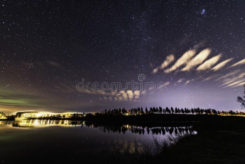 Startar svagt Aurora vid nästan klar himmel, små moln som fjädrar ovanför sjön på den skandinaviska landsbygden royaltyfri fotografi