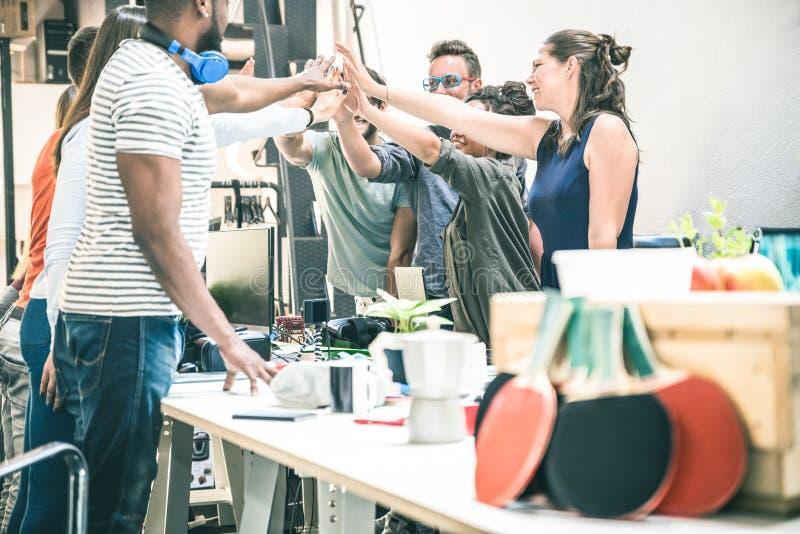 Startarbeitskräfte des jungen Angestellten gruppieren das Stapeln von Händen im Büro stockfotografie