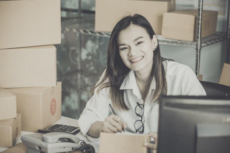 Startarbete på arbetsplatsföretagsägareleendet förbereder sig lyckligt att leverera packat in i papp för att leverera kunder, fotografering för bildbyråer