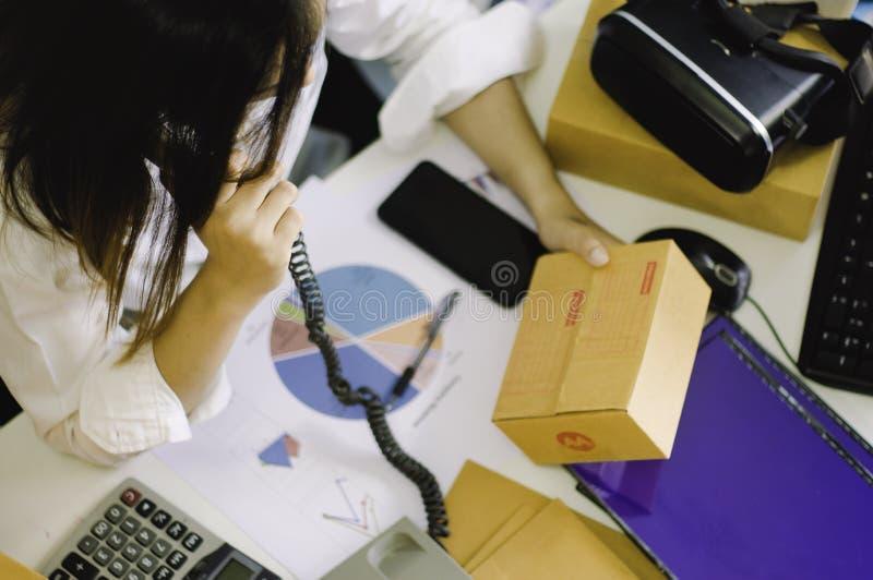 Startarbete på arbetsplatsföretagsägaren förbereder sig att leverera vrhörlurar med mikrofon som packas in i papp, för att levere royaltyfri fotografi