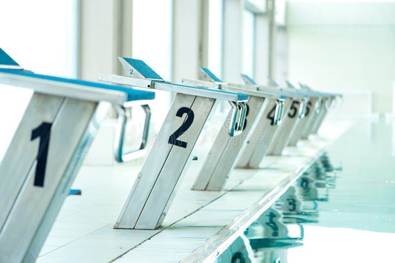 Startblöcke in einem Swimmingpool lizenzfreie stockbilder