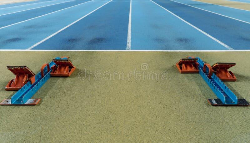 Startblöcke für einen Sprintlauf auf einer Bahn lizenzfreie stockfotos