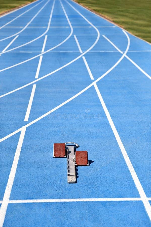 Startblokken op blauwe renbanenstegen bij spoor en gebied Sporttoebehoren Verticaal gewas van stadionvloer met exemplaarruimte stock afbeeldingen