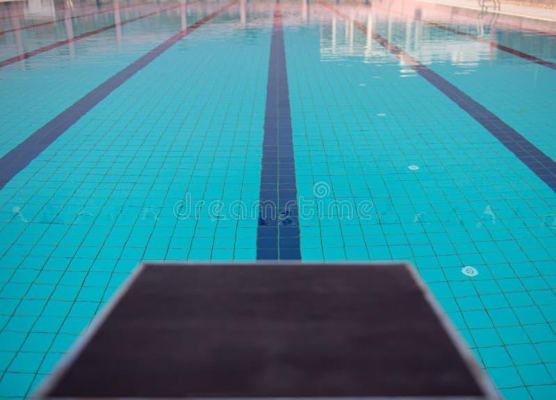 Startblokken in rij door het zwembad, selectieve nadruk Sprongplatform voor het zwemmen in zwembad en tribune backgroun stock foto's