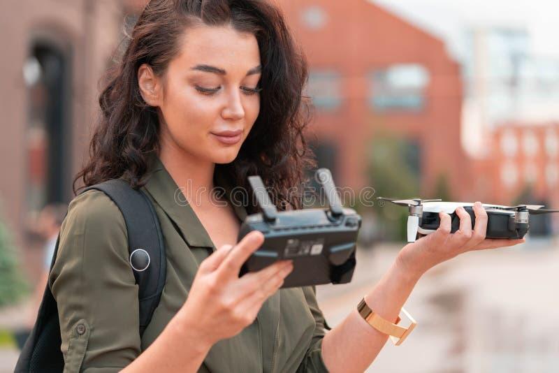 Startendes quadcopter Brummen der jungen Schönheit am städtischen Hintergrund lizenzfreies stockfoto