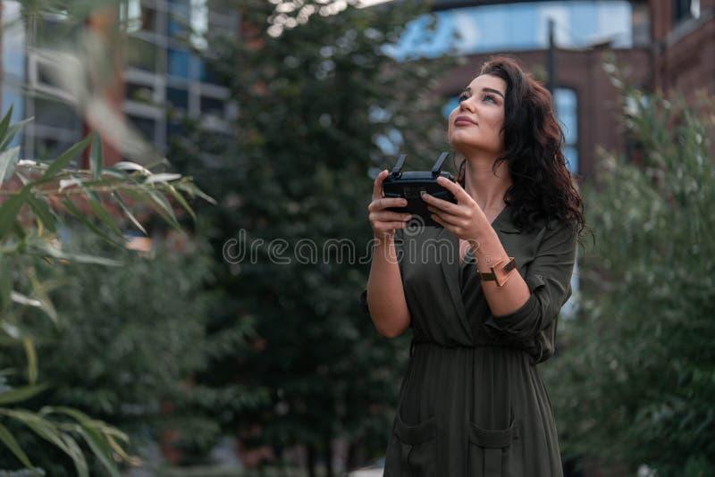 Startendes quadcopter Brummen der jungen Schönheit am städtischen Hintergrund stockfoto
