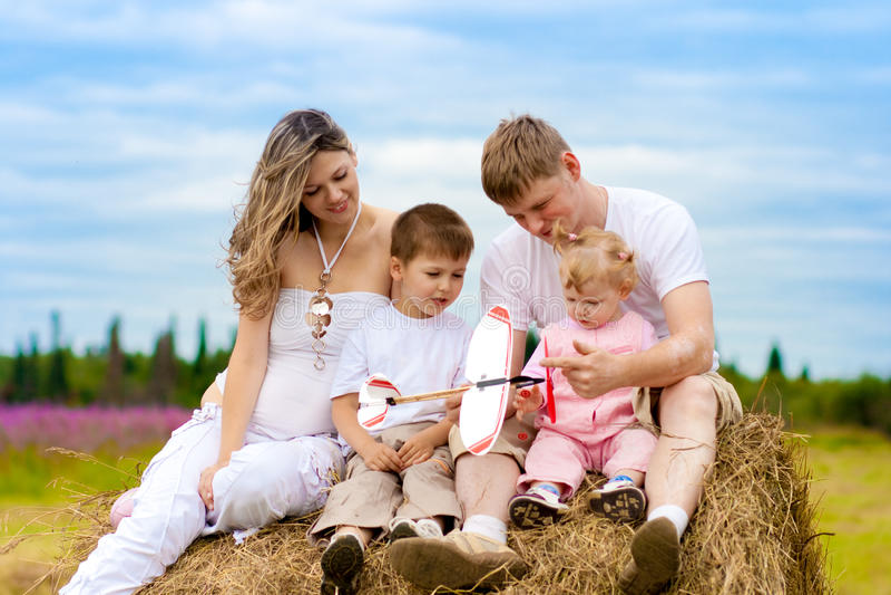 Startendes Spielzeug der glücklichen Familie, das auf Heuschober sitzt stockbild