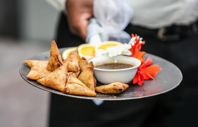 Starter food being offered by waiter. Samosas on a plate. Samosa being served. Starters served in a pan royalty free stock photo