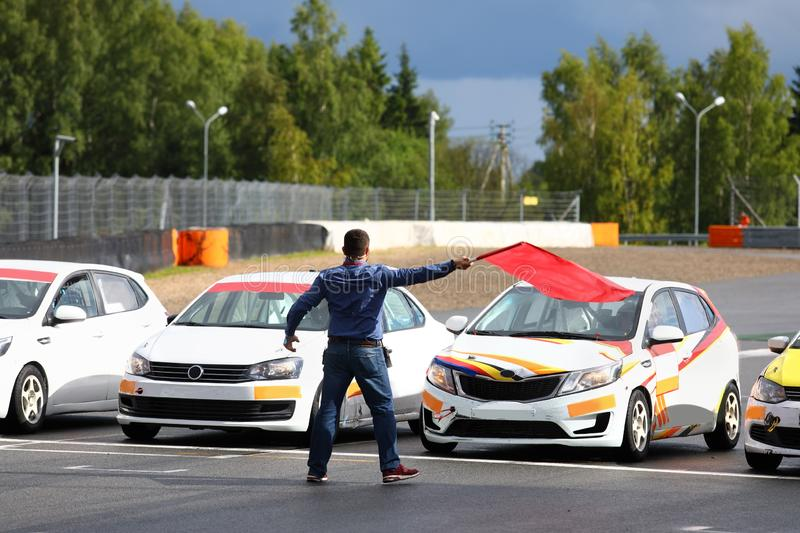 Starter gives the go-ahead red flag to start car racing. Starter man gives the go-ahead red flag to start car racing stock images