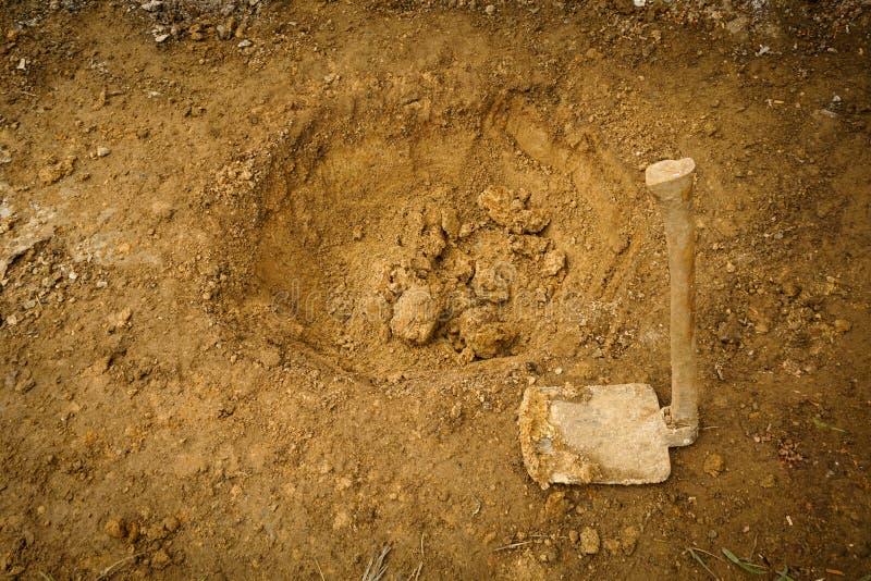 Starter som gräver ett hål med en tagen smutsig hacka i Bogor Indonesien arkivbild