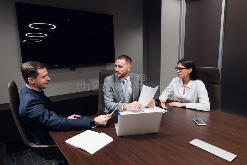 Startgeschäft, kreative Geschäftsleute des unterschiedlichen Alters und Rennen erfassen in Konferenzzimmer im dunklen modernen Bü stockbilder